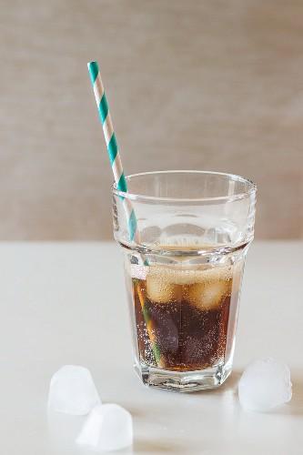 Glas Cola mit Eiswürfeln und Retro-Strohhalm