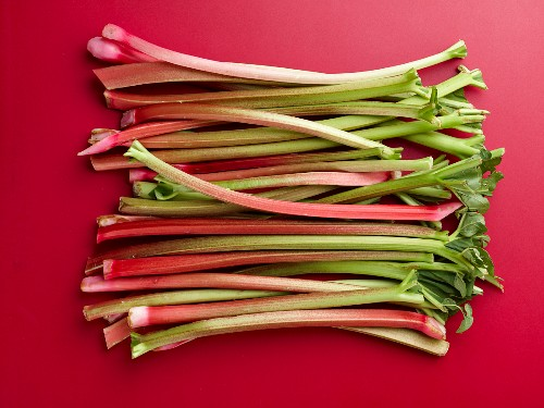 Rhubarb stalks on a red surface