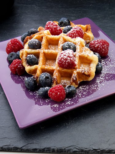 Waffles with fresh berries and icing sugar