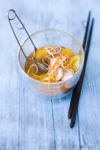 A glass of chicken noodle soup with galangal and spices in a tea infuser