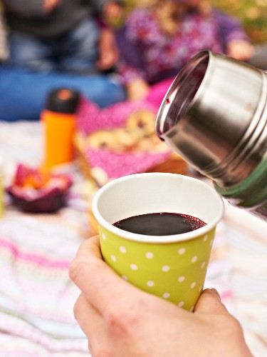 A woman pouring elderberry juice from a thermos flask into a paper cup