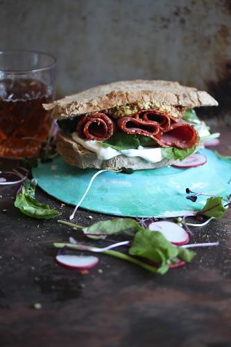 Vollkorn Sandwich mit Salami, Salat, Remoulade und Senf