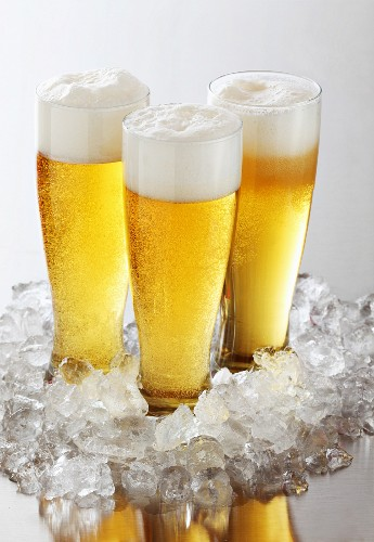Three glasses of beer with foam on crushed ice
