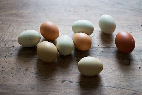 Various different coloured hens' eggs on a wooden surface