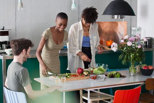 Friends preparing salad in a kitchen