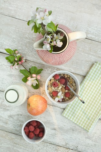 Muesli with nuts, apples, raspberries and milk on a wooden table (seen from above)