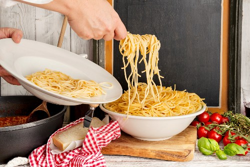 A person helping themselves to spaghetti