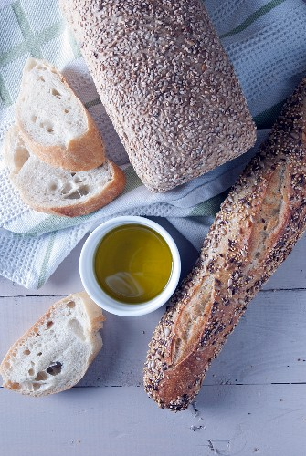 Seeded bread, baguette and olive oil (seen from above)