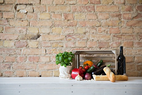 An arrangement of fresh vegetables, basil, red wine and baguette against a stone wall