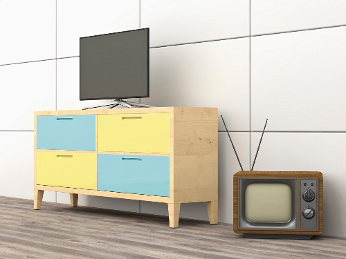 An antique television next to a modern sideboard with a flat-screen television