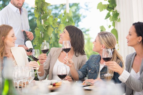 Young women tasting red wine at a table outside with the waiter presenting a bottle of wine