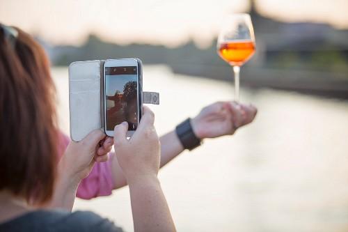 Frau fotografiert Getränk mit ihrem Smartphone