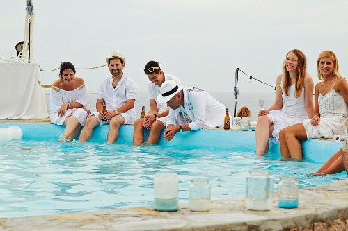 Wedding guests in summer clothes sitting by the side of a pool