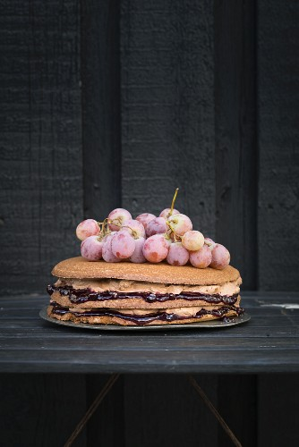 Chocolate cake with grape jam, chocolate cream and red grapes