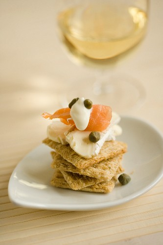 A stack of crackers topped with soft cheese, salmon and capers served with white wine