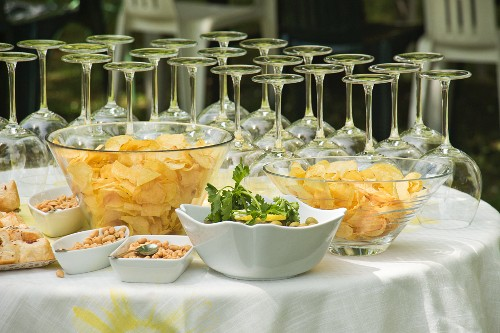 An aperitif buffet with wine glasses, crisps, olives and peanuts