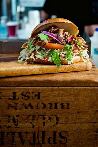 Pulled Pork Burger mit Salat und Essiggurken auf einem Marktstand in London