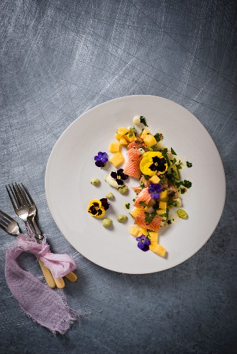 Smoked trout on a mango salad with wasabi cream and edible flowers