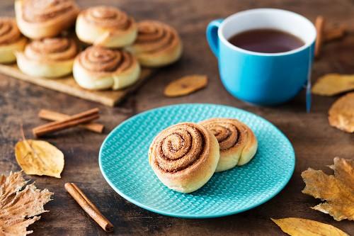 Cinnamon bun on a plate with a cup of tea