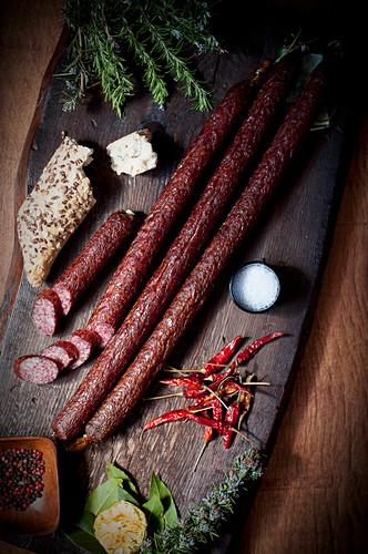Lange Schweinewürste mit Leinsamenbrötchen und getrockneten Chilischoten auf Holzschneidebrett