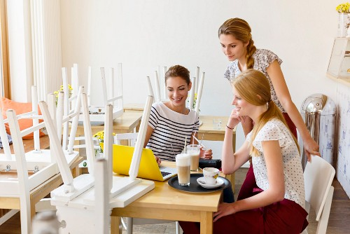 Three women having a meeting in a cafe around a laptop