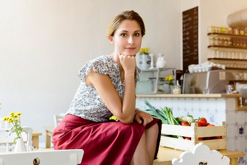A young woman sitting at a table in a cafe