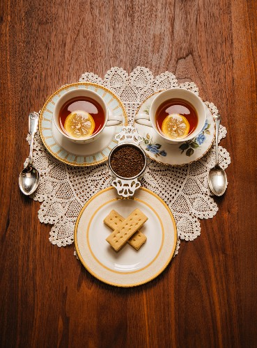A teatime face made from cups of tea and shortbread