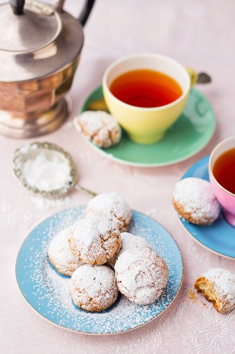 Almond biscuits with icing sugar served with tea