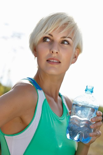 A young blonde woman wearing sports clothing with a bottle of water