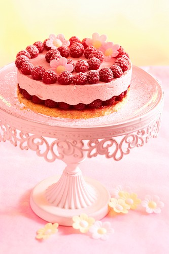 A mini raspberry cake on a pink cake stand