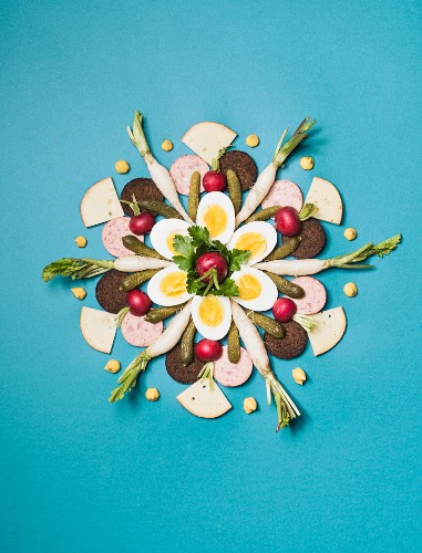 Supper ingredients arranged in a flower shape on a blue surface