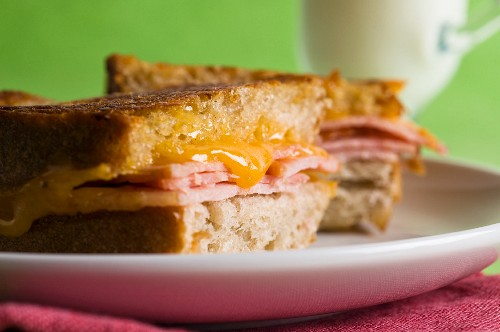 A grilled cheese sandwich made with Canadian cheddar and back bacon with a glass of milk in the background