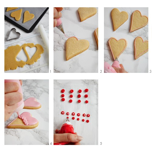 Heart-shaped biscuits being iced in pink