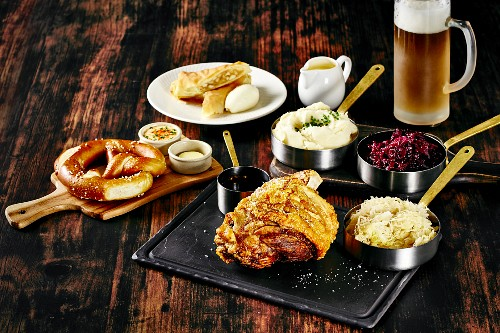 Oktober Fest food: pretzel, pork knuckle with side dishes and beer