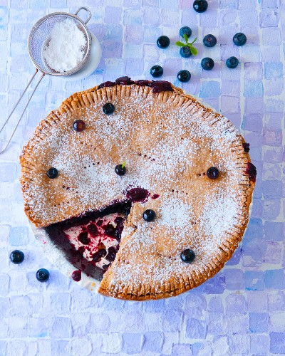 Blueberry pie with icing sugar, sliced