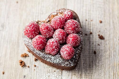A mini heart-shaped chocolate cake with raspberries (gluten free)