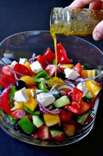 Dressing being poured over a vegetable salad