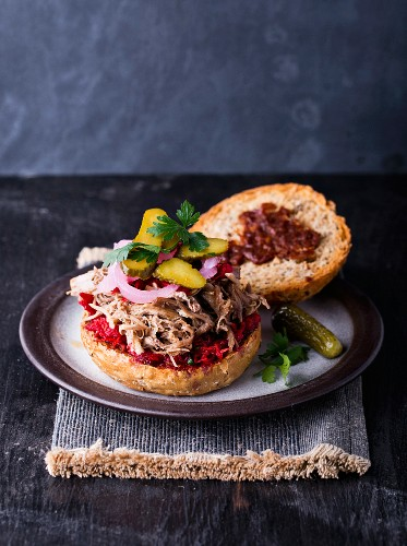 A pulled pork burger with gherkins and onions