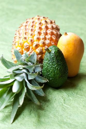 A pineapple, an avocado and a mango