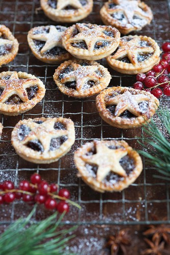 Homemade mince pies with star lids and icing sugar on a cooling rack