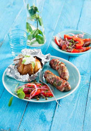Sausages wrapped in Parma ham with sage served with a tomato salad and a baked potato