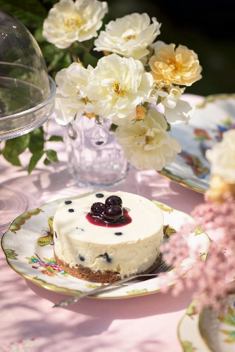 A small cheesecake with blueberries on the garden table