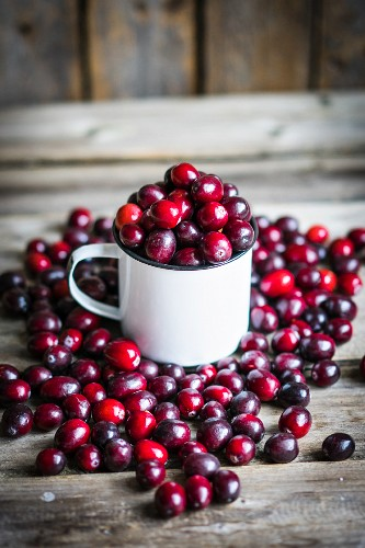 Cranberries in a mug and on a rustic wooden surface