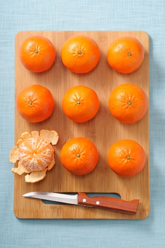 Whole mandarins and a peeled mandarin on a wooden board