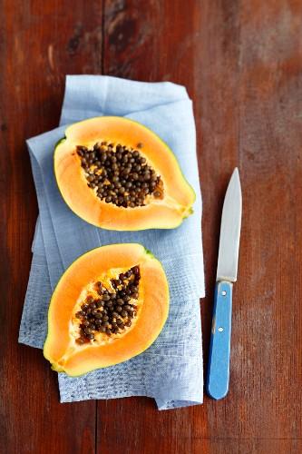 Papaya halves on a blue linen napkin