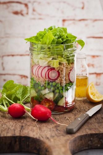 Schichtsalat mit Erbsen, Radieschen, Gurke und Tomate im Glas