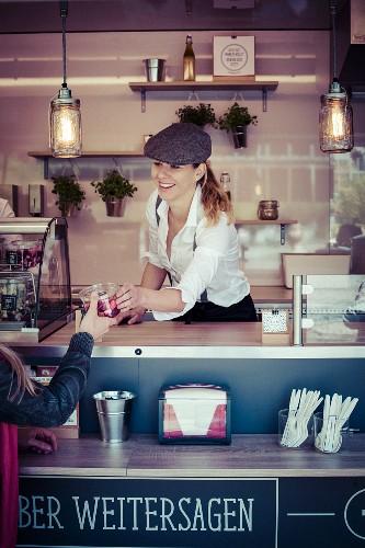 Junge Frau verkauft Snack im Food Truck