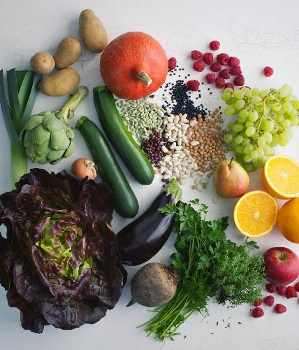 Gemüsestillleben mit Obst, Kräutern und Hülsenfrüchten
