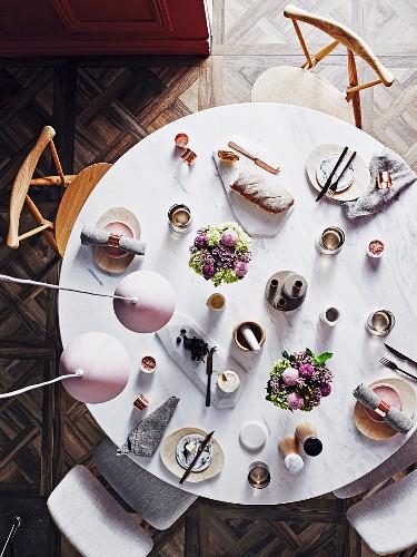 Gedeckter runder Marmortisch mit Pastellfarbenem Blumenschmuck aus der Vogelperspektive