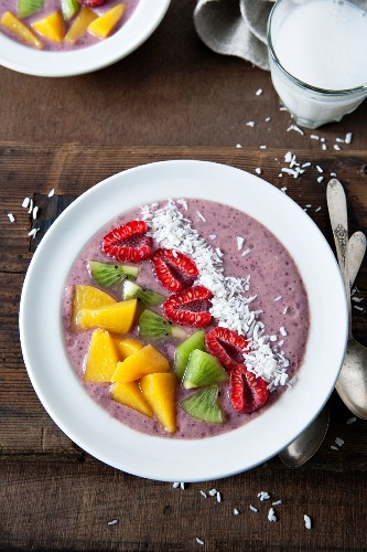 A smoothie bowl with blueberries, banana and apple garnished with raspberries, kiwi, peach and coconut